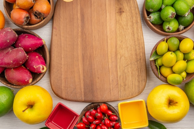 Vista de cima diferentes frutas frescas dentro de pratos no fundo branco tropical cor madura dieta suave exótica vida saudável