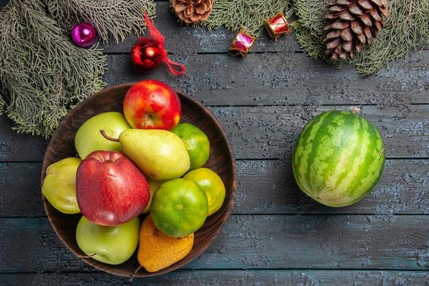 Vista de cima diferentes frutas frescas dentro do prato na mesa azul-escuro composição de cores de frutas frescas maduras