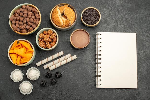 Vista de cima diferentes ingredientes cips, flocos e nozes na superfície cinza refeição lanche cor do café da manhã