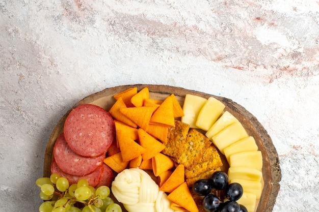 Vista de cima diferentes lanches cips, salsichas, queijo e uvas frescas no piso branco