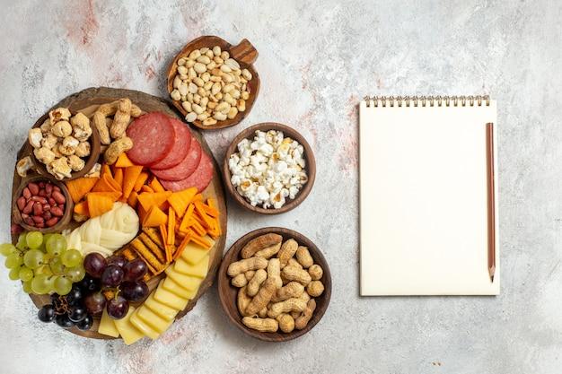Vista de cima diferentes lanches nozes cips uvas, queijo e salsichas em um fundo branco claro, nozes, lanches, frutas