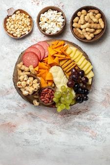 Vista de cima diferentes lanches nozes cips uvas, queijo e salsichas em uma superfície branca clara, porca, lanche comida frutas