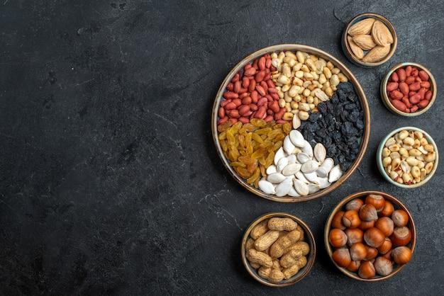 Vista de cima diferentes nozes com passas e frutas secas em um lanche de porca de mesa cinza nozes com passas de frutas secas