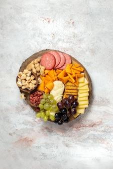 Vista de cima diferentes petiscos nozes cips uvas queijo e salsichas na superfície branca porca petisco comida frutas