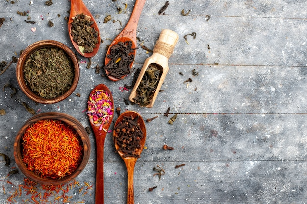 Vista de cima diferentes sabores de chá seco fresco no chão cinza chá fruta planta sabor flor