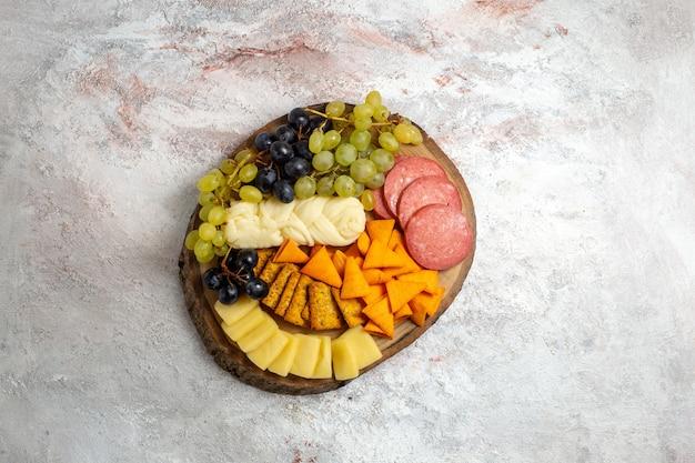 Vista de cima diferentes salgadinhos cips, salsichas, queijo e uvas frescas no espaço em branco