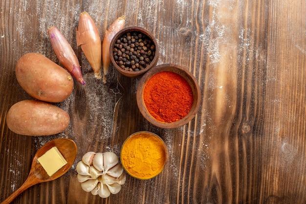 Vista de cima diferentes temperos com batatas frescas em especiarias cruas de produtos de mesa de madeira