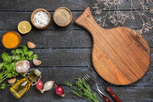 Vista de cima diferentes temperos com óleo e verduras na mesa escura