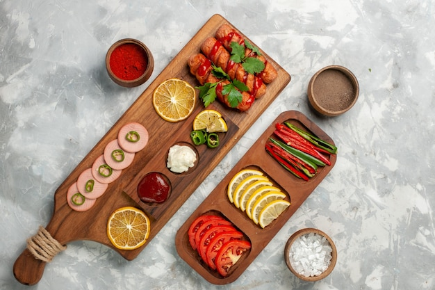 Vista de cima diferentes temperos com salsichas e vegetais na mesa branca.