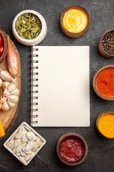 Vista de cima diferentes temperos com sementes e bloco de notas em fundo escuro cor de pimenta picante de sementes