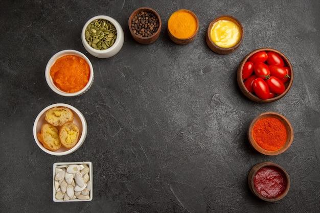 Vista de cima diferentes temperos com tomates em fundo escuro de cor pimenta picante fruta