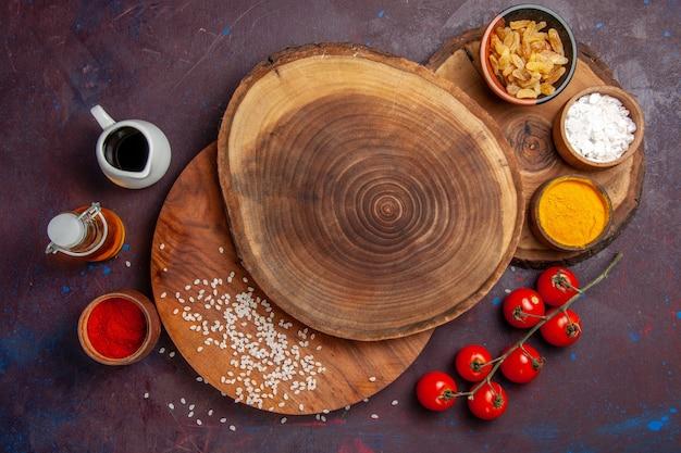 Vista de cima diferentes temperos com tomates em fundo escuro refeição com temperos picantes