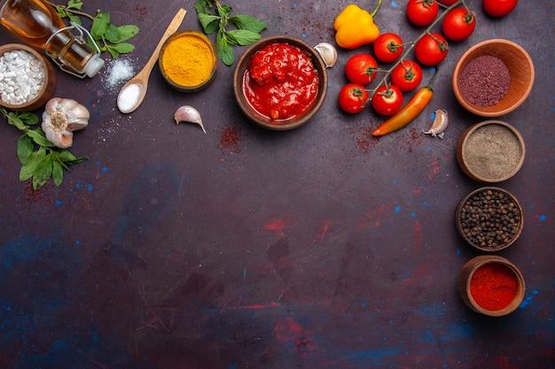 Vista de cima diferentes temperos com tomates frescos no espaço escuro