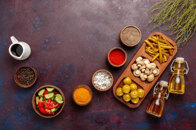 Vista de cima diferentes temperos com vegetais e óleo na mesa escura