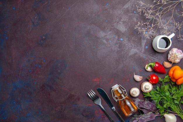 Vista de cima diferentes temperos com vegetais frescos em uma superfície escura salada de pimenta picante saúde