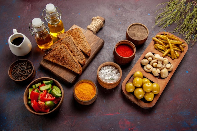 Vista de cima diferentes temperos com vegetais, pão, pão e óleo na mesa escura