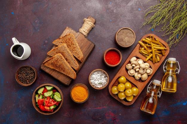 Vista de cima diferentes temperos com vegetais, pão, pão e óleo na superfície escura