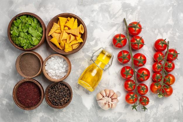 Vista de cima diferentes temperos com verduras e óleo na mesa branca
