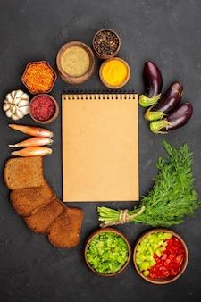 Vista de cima diferentes temperos com verduras e pães escuros em fundo escuro para salada tempero refeição de pão saúde