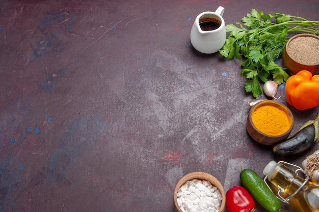 Vista de cima diferentes temperos com verduras e vegetais em um fundo escuro