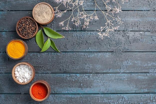Vista de cima diferentes temperos dentro de pequenos potes em uma mesa azul-escura com pimenta picante comida ousada