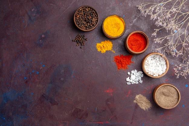 Vista de cima diferentes temperos dentro de potes no fundo escuro sopa de molho de sopa comida picante de pimenta