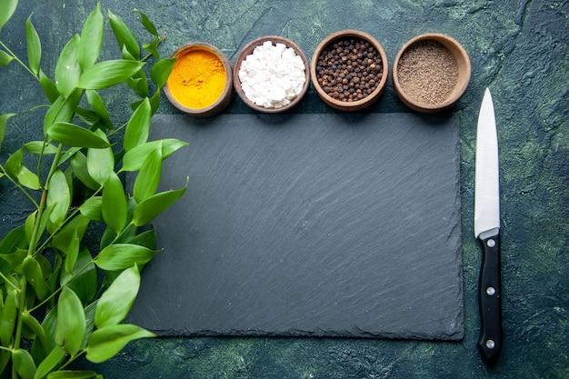 Vista de cima diferentes temperos na superfície azul escuro comidas especiarias sal pimenta foto cor