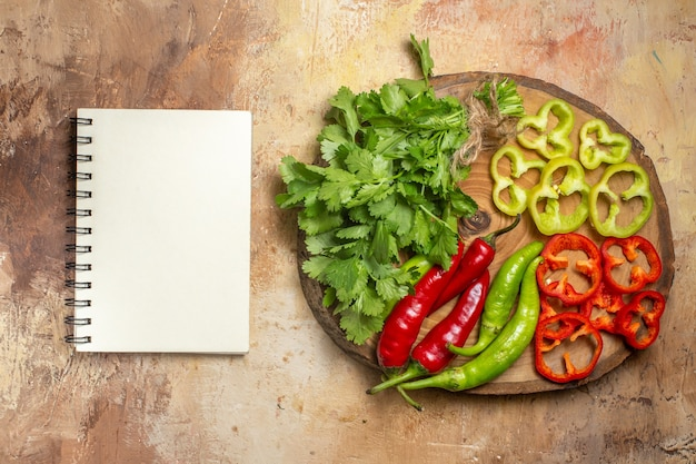 Vista de cima, diferentes vegetais, coentro, pimenta, pimentões, pimentões, cortados, em, pedaços, em, redondo, madeira, board, um, notebook, em, âmbar background.
