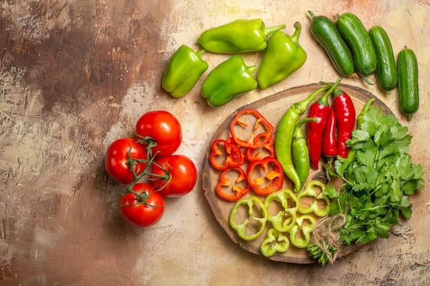 Vista de cima diferentes vegetais cortados em pedaços em tábua de madeira redonda tomates pepinos em fundo amarelo ocre