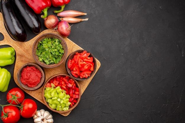 Vista de cima diferentes vegetais frescos e maduros na refeição saudável saudável de salada de fundo cinza
