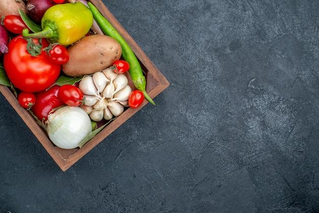 Vista de cima diferentes vegetais frescos na mesa de cor escura salada de vegetais frescos maduros