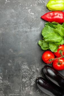 Vista de cima diferentes vegetais, tomates, pimentões, beringelas, fundo cinza