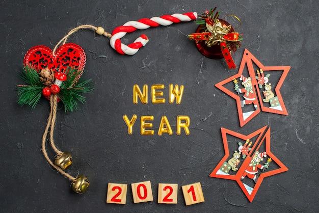 Vista de cima do ano novo em um círculo de diferentes enfeites de natal, bloco de madeira doce na superfície escura e isolada