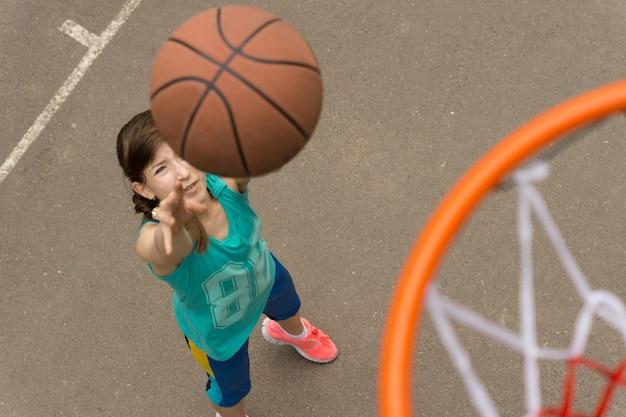Vista de cima do aro e da rede de uma jovem adolescente atirando para um gol no basquete