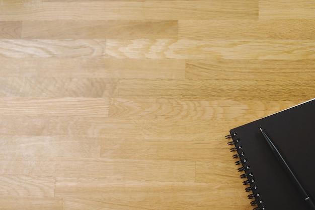 Vista de cima do bloco de notas de esboço de rosto preto e uma caneta na mesa de madeira com espaço de cópia. caderno e texto em branco de vista superior.