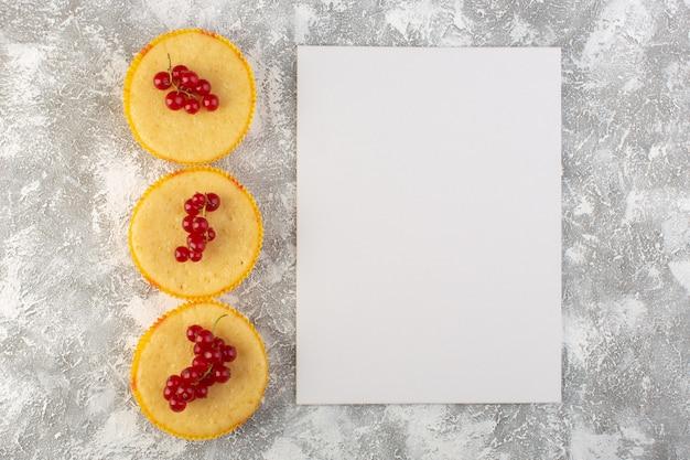 Vista de cima do bolo com cranberries gostosos e perfeitamente assados com papel em branco no fundo claro.