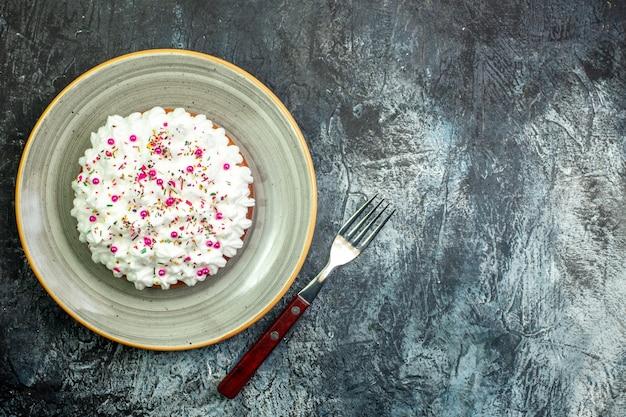 Vista de cima do bolo com creme de confeiteiro branco no garfo de prato redondo cinza na mesa cinza com local de cópia