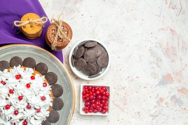 Vista de cima do bolo com creme de confeiteiro em prato oval, biscoitos de xale roxos amarrados com corda de chocolate e frutas em tigelas