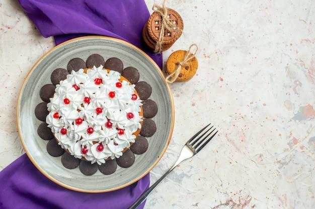 Vista de cima do bolo com creme de confeiteiro em prato oval xale roxo biscoitos amarrados com um garfo de corda na mesa branca