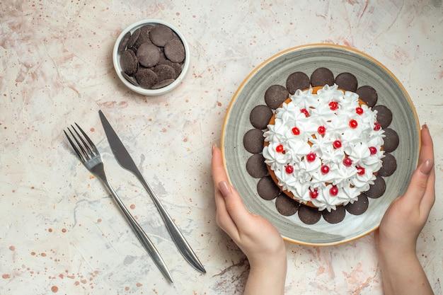 Vista de cima do bolo com creme de confeiteiro no prato, mão feminina, chocolate, garfo tigela e faca de jantar