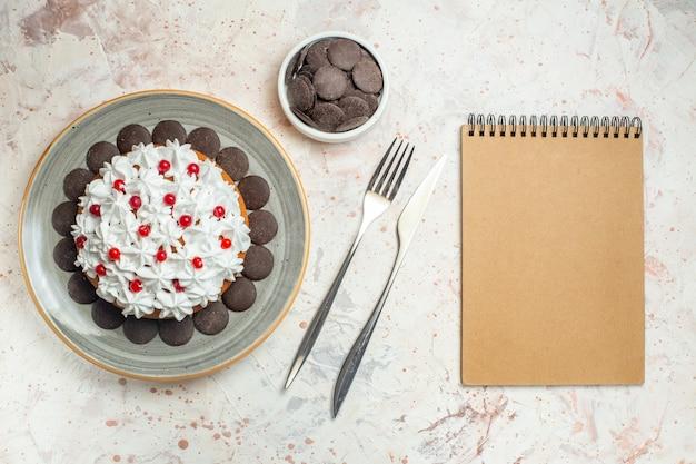 Vista de cima do bolo com creme de confeiteiro no prato oval de chocolate no garfo de tigela e faca e caderno
