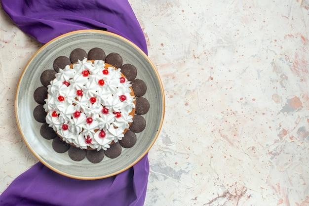 Vista de cima do bolo com creme de confeiteiro no prato xale roxo