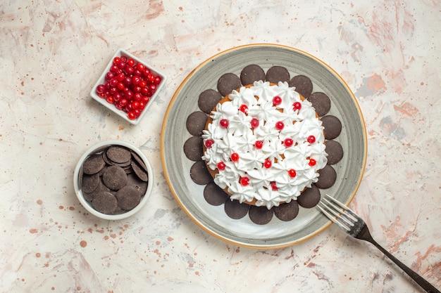 Vista de cima do bolo com creme de frutas e chocolate no garfo de tigelas