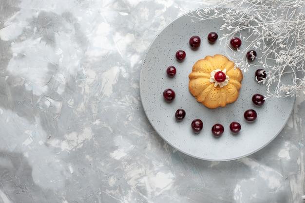 Vista de cima do bolo com creme e cerejas frescas em uma mesa leve, biscoito de bolo, biscoito doce