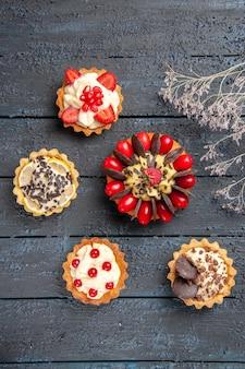 Vista de cima do bolo com fruta cornel, framboesa, chocolate redondo e tortas na superfície de madeira escura