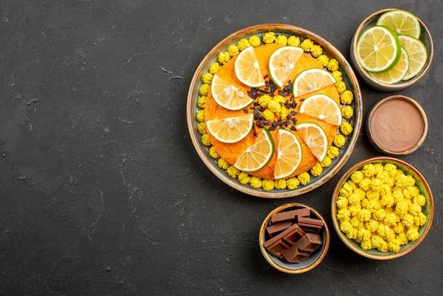 Vista de cima do bolo com frutas cítricas bolo apetitoso com chocolate e frutas cítricas ao lado das tigelas de fatias de chocolate com limão e creme de chocolate na mesa preta