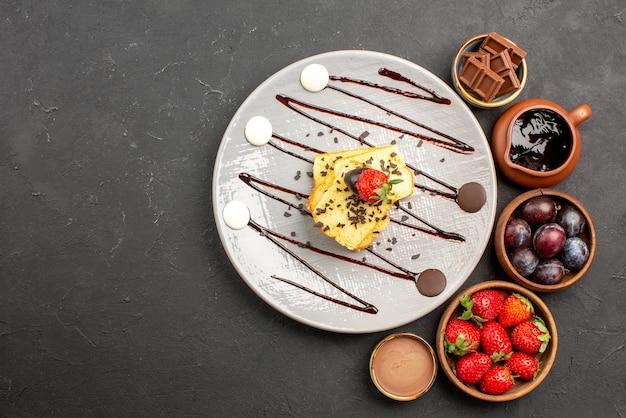 Vista de cima do bolo com morango, morango, chocolate e frutas vermelhas em tigelas e prato de bolo com morangos e calda de chocolate na mesa