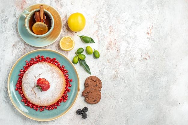 Vista de cima do bolo com morangos, uma xícara de chá preto com canela e limão ao lado do prato de bolo com morangos e sementes de biscoitos de chocolate com romã na mesa