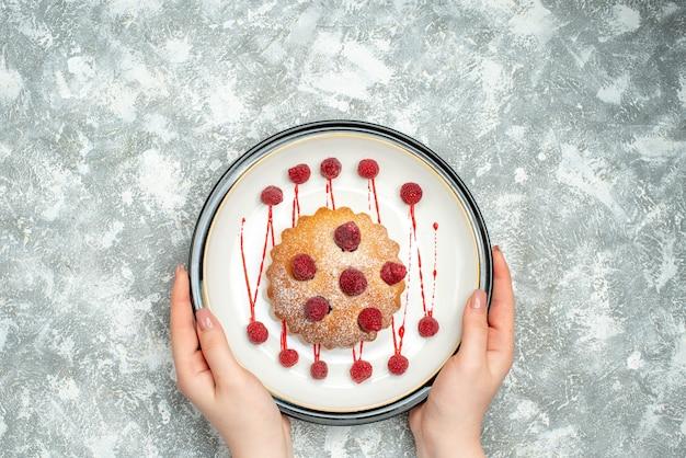 Vista de cima do bolo de frutas vermelhas em um prato oval branco em uma mão feminina em um espaço livre de superfície cinza