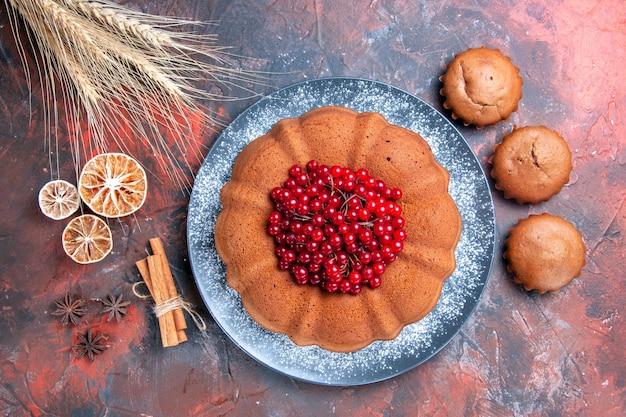 Vista de cima do bolo e cupcakes um bolo apetitoso cupcakes espigas de trigo canela em pau limão